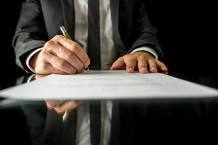 financial official: Front view of businessman signing important legal document on black desk with reflection.