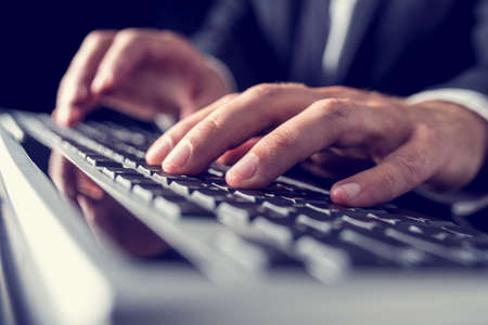 Retro vintage or instagram style image of a businessman typing on computer keyboard.  photo