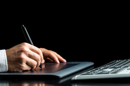 Closeup of male graphic designer working on his digital tablet over black background.