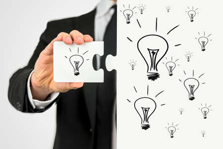 Businessman with the idea for business development holding a puzzle piece with lightbulb on it to perfect his idea. photo