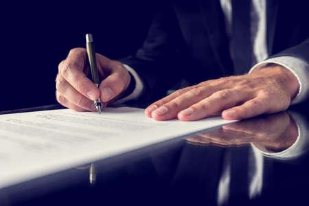 Image rétro de l'avocat signant un document juridique important sur le bureau noir. Sur fond noir.