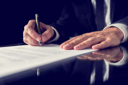 financial agreement: Retro image of lawyer signing important legal document on black desk. Over black background. Stock Photo