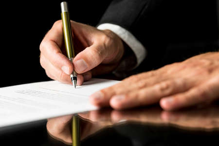 Closeup of male hand signing legal or insurance document on black desk with reflection.