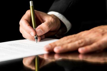 firmando: Detalle de mano masculina firmar documento legal o seguro sobre el escritorio negro con la reflexi�n.