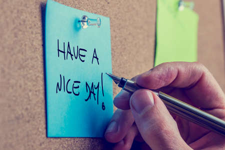 Closeup of male hand writing Have a nice day message on a blue post it paper pinned to a cork bulletin board photo