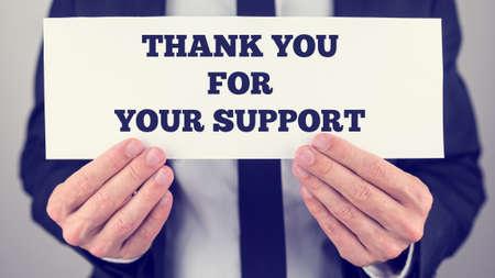 amabilidad: Efecto retro se desvaneci� y la imagen en tonos de un hombre de negocios que sostiene la tarjeta blanca con Gracias por su se�al de apoyo en �l. Foto de archivo