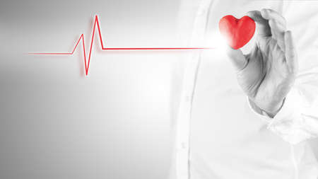 Healthy heart and cardiology concept with a cardiogram linked to red heart. photo