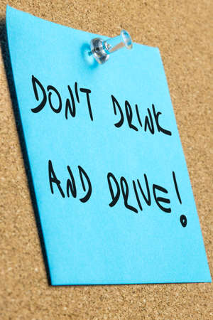 Dont drink and drive sign written on blue post it paper pinned to a cork bulletin board.