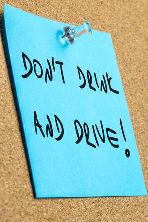 dont drink and drive: Dont drink and drive sign written on blue post it paper pinned to a cork bulletin board.