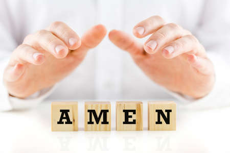 divinity: Male hands making protective gesture over wooden cubes carrying Amen sign. Stock Photo