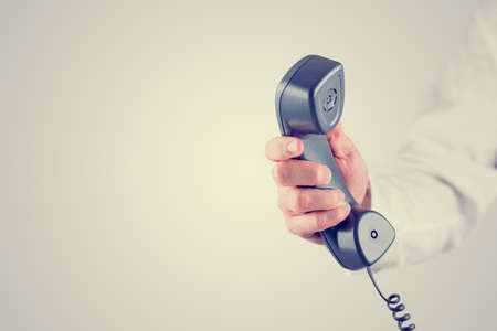 Retro effect faded and toned image of a male hand holding landline telephone receiver with empty space ready for your text. Stock Photo