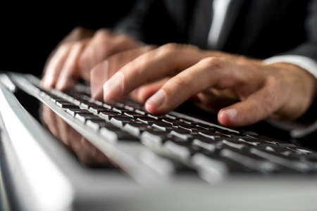 Close-up with motion blur effect of the hands of a man wearing business suit while typing fast on a desktop computer black keyboard. photo