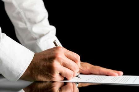 compromiso: Primer plano de las manos de un hombre que llevaba camisa blanca mientras que la firma con un lápiz un documento en papel oficial o acuerdo, colocados sobre una mesa de reflexión negro, con el espacio de la copia en fondo negro.