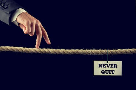 Businessman walking his finger along a frayed rope toward Never quit sign. Conceptual of business and education and determination in life, retro effect faded look. Stock Photo