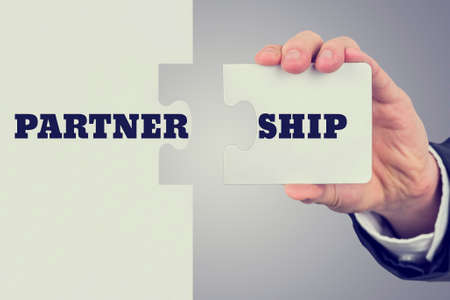 partnership power: Retro image of male hand holding piece of puzzle to create a word Partnership. Concept of importance of teamwork and cooperation. Stock Photo