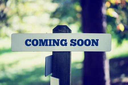 Rustieke bord met de woorden Binnenkort verkondigen een verwachte en wachtte komende evenement buiten in het bos.