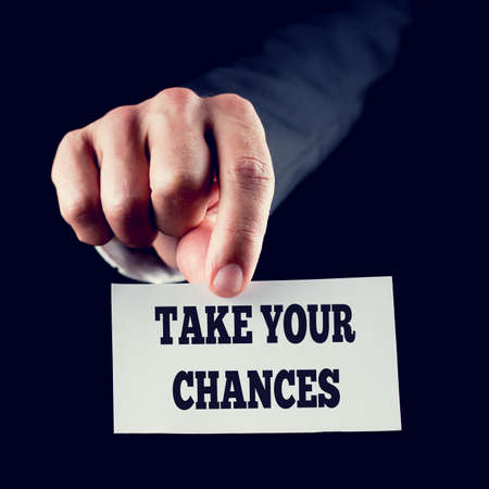 contingent: Businessman in a suit holding out a small white card with the motivational message and words - Take Your Chances
