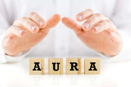 aura energy: Word - Aura - on wooden cubes with a man in a white shirt holding his hands cupped protectively over the top in an inspirational and spiritual concept.