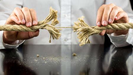 リスクと逆境の概念では両手でそのまま 1 つの残りの文字列を持つ擦り切れているロープを保持している男。