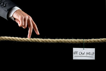 warranty questions: We Can Help concept with a hand written note bearing the words hanging on a wire from a rope suspended over a black background with a businessman walking his fingers along it like a tightrope. Stock Photo