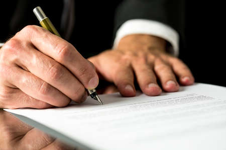 fountain pen: Close up of the hands of a businessman signing a typed document with a fountain pen with copyspace in the foreground.