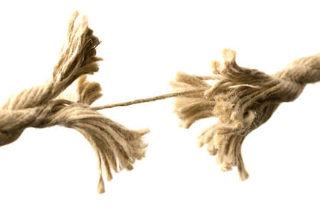 Close-up of a rope splitting apart held together by one last thread, concept of fragility and division, with copy space on white  Stock Photo