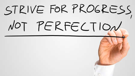 1: Man writing the idiom - Strive For Progress Not Perfection - on a virtual interface with a black marker pen over grey with copyspace in a motivational business message
