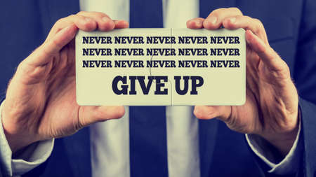 urge: Close-up of the hands of a man wearing business formal suit, with white shirt and tie, while holding two joined jigsaw puzzle pieces with the inspirational message and urge to never give up