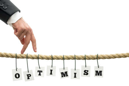 majuscule: Hand of a business man making the walking gesture on a rope with hanging tags with black majuscule letters forming the word optimism, with copy space on white  Stock Photo