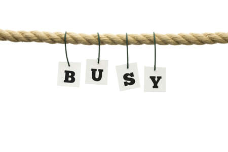 swamped: White tags with black capital letters forming the word busy, hanging on a rope, with copy space on white  Stock Photo