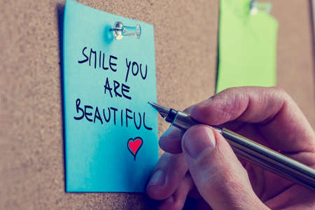 post it: Romantic boyfriend writing Smile you are beautiful message on a blue  Stock Photo