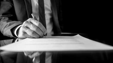 businessman signing documents: Black and white low angle image of the hand of a businessman in a suit signing a document or contract with a fountain pen on a reflective surface