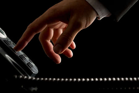 initiating: Close-up of the hand of a businessman dialing or initiating a phone call by operating the keypad of a desk corded land line telephone, on black