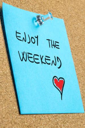 weekend activities: Perspective close-up of a blue reminder with handwritten wish to enjoy the weekend and a red heart shape, pinned on a wooden board, concept of spare time, love and recreation
