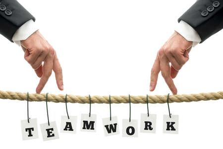combined effort: Teamwork in business concept with the letters spelling Teamwork individually suspended by wire from a rope with two men walking their fingers towards each other on top, over white  Stock Photo