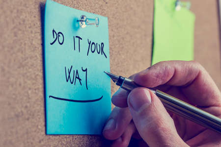 oneness: Retro image of the hand of a man holding a pen over a blue reminder with the inspirational advice to do it your way, pinned on a wooden board.