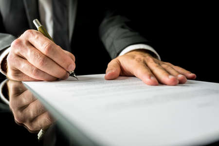 lawyer: Close up low angle of the hands of a businessman in a suit signing a paper document with a fountain pen on a reflective desk top.