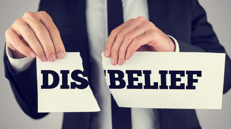 opposites: Man holding a torn paper sign in his hands with the words - Dis - Belief - spread over the two halves depicting the concept of opposites - Belief and Disbelief.