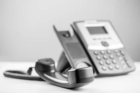 라인을 효과적으로 차단하거나 전화를 받기 위해 사람이 도착할 때까지 기다리는 전화 수신기의 그레이 스케일 이미지. 스톡 콘텐츠