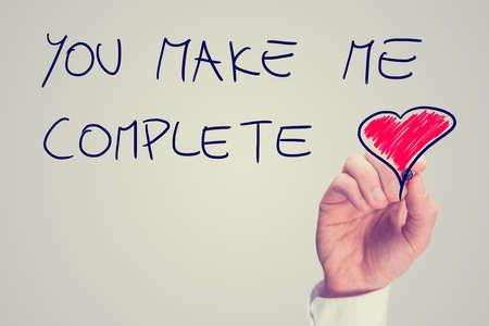 Man het schrijven van een inspirerende boodschap van liefde op een virtuele-interface met de woorden - You Make Me Complete - met een rood hart en copyspace, retro effect vervaagde look. Stockfoto