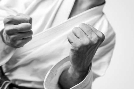 practicing: Black and white close up image of the bare fists of a man dressed for martial arts during training or in combat.