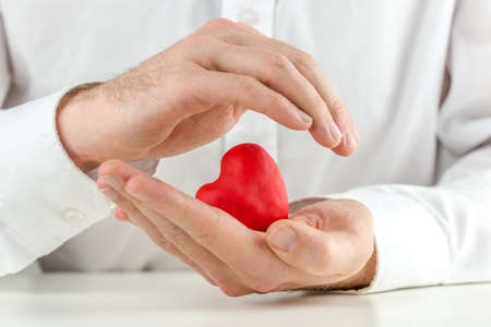 Caring man cupping a red heart in his hands with one hand held protectively over the top in a love, romance and nurturing concept.