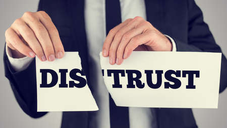 distrust: Businessman tearing up a sign saying - Distrust - conceptual image importance of trust and cooperation in successful business.