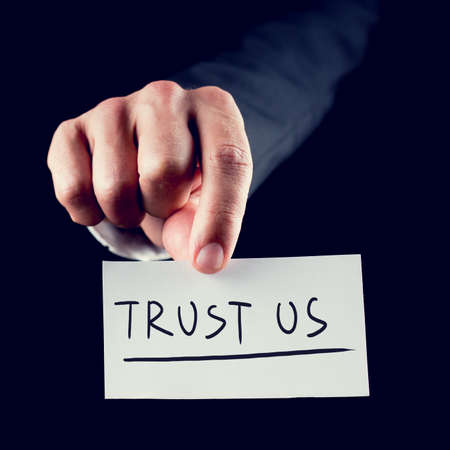 Retro style image of a hand holding piece of paper up close with TRUST US written on it