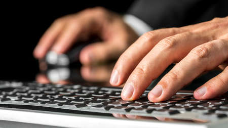 Close up low angle view of the left hand of a man typing on a computer keyboard inputting data with his other hand on the mouse in the background. photo