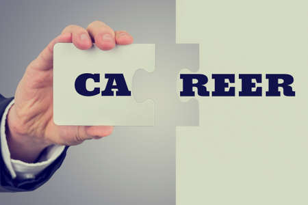 making decision: Businessman holding two matching puzzle pieces with the word - Career - spread over them in a concept of achievement, challenge, solution and success.