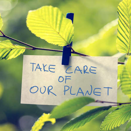 Take Care of our Planet concept with a handwritten note attached to a twig of fresh green sunlit leaves by a wooden clothes peg depicting the conservation of the ecology and natural resources. photo