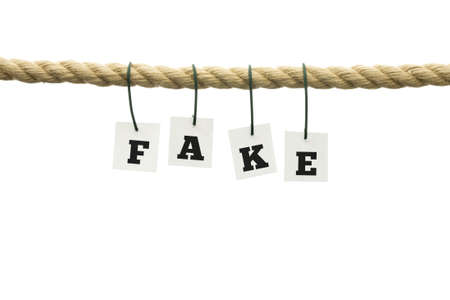 deceiving: Word - Fake - suspended from a rope with each individual letter attached by a wire conceptual of something that is neither authentic nor genuine, over white with copyspace.