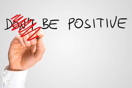 eagerness: Concept of positivity and optimism - male hand changing a Dont be positive into a Be positive sign. Stock Photo