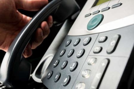 Closeup of landline office telephone with male hand holding its receiver.